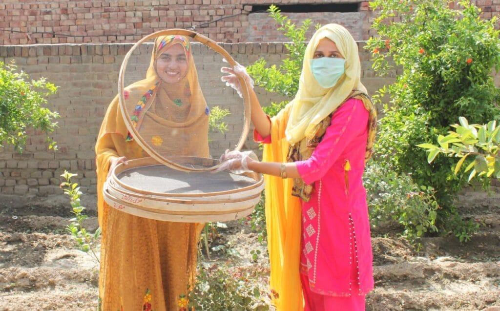 Women holding farm equipment