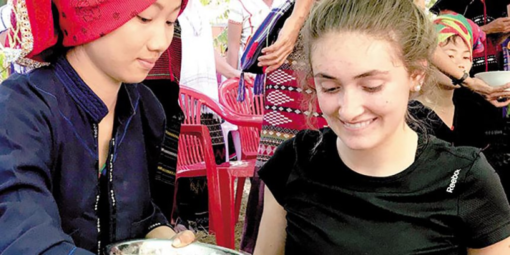 Ashlyn Shantz of Heidelberg, Ont. shares a meal with a local in the village of Win Poat, Myanmar.